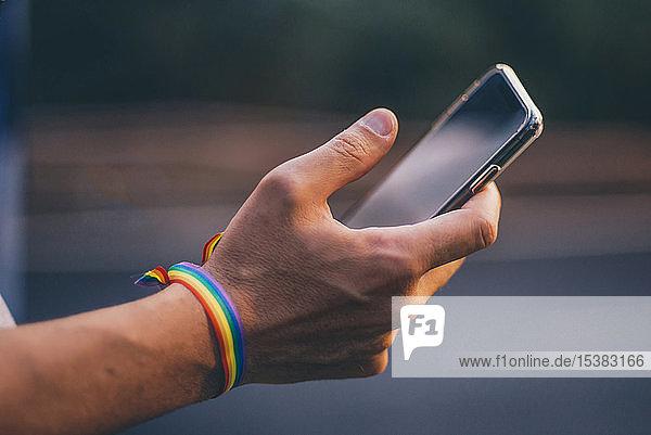 Hände eines Mannes mit Pusera-Gay-Flagge  der ein Smartphone hält