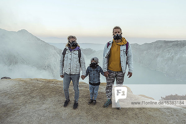 Family with respirator masks standing hand in hand at the edge of volcano Ijen  Java  Indonesia