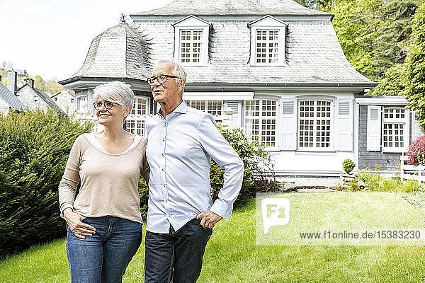 Lächelndes älteres Ehepaar steht im Garten seines Hauses