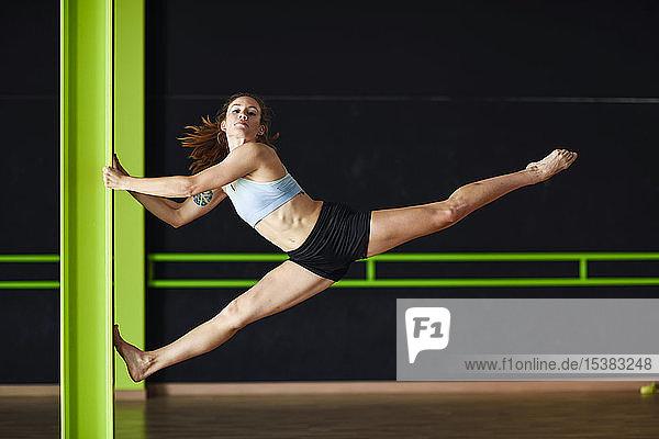Sportliche junge Frau macht Hallenakrobatik