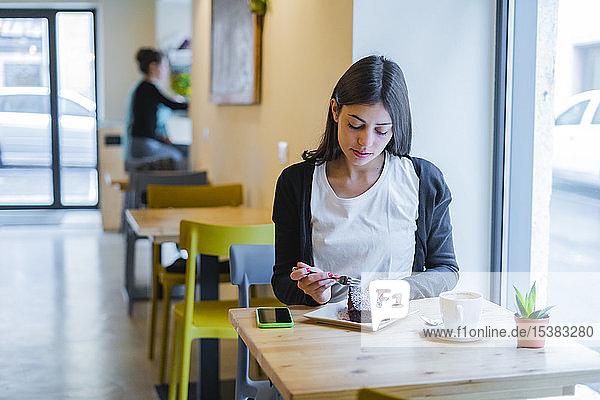 Junge Frau in einem Café  die ein Stück Kuchen isst