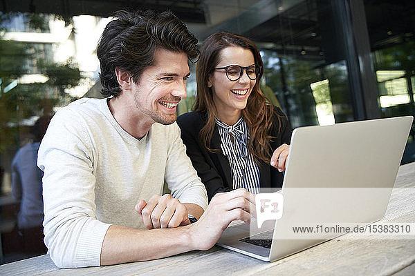 Glücklicher Geschäftsmann und Geschäftsfrau mit Laptop-Treffen in der Stadt