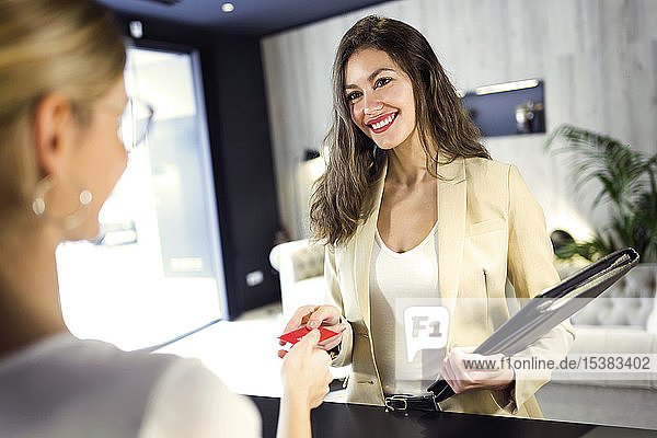 Smiling businesswoman handing over credit card at reception