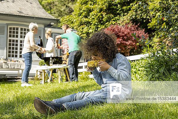 Junge isst einen Maiskolben auf einem Familiengrill im Garten