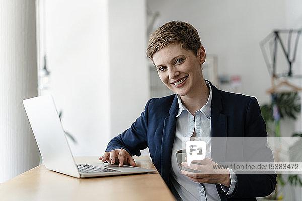 Porträt einer lächelnden Geschäftsfrau mit Laptop in einem Cafe