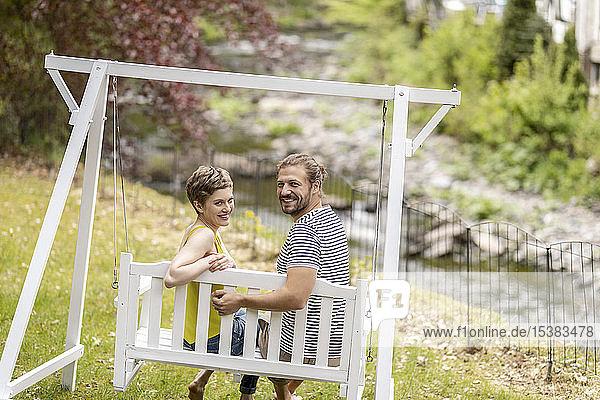 Porträt eines lächelnden Paares  das auf einer Baldachinschaukel im Garten sitzt