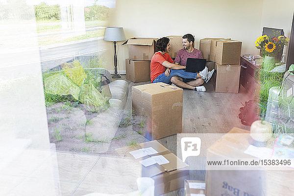 Glückliches Paar zieht mit Laptop in ein neues Heim ein