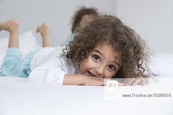 Porträt eines glücklichen Jungen mit seinem Bruder im Bett