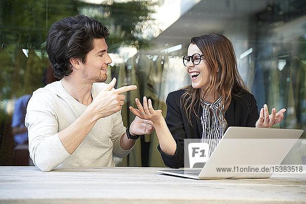 Geschäftsmann und glückliche Geschäftsfrau mit Laptop treffen sich in der Stadt