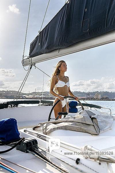 Young woman navigating catamaran on a sailing trip