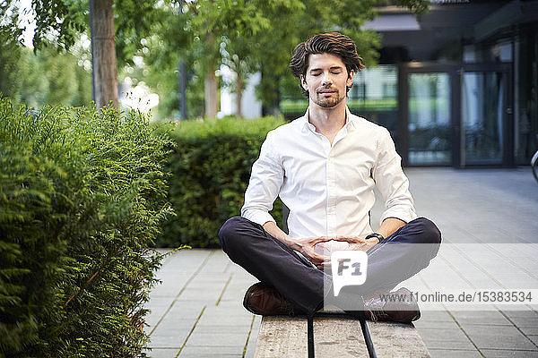 Geschäftsmann beim Yoga auf einer Bank in der Stadt