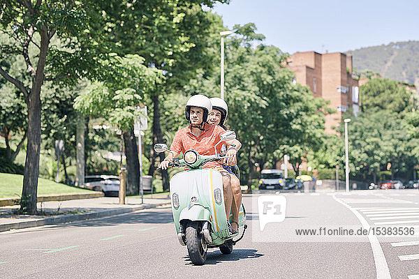 Junges Ehepaar fährt einen Oldtimer-Motorroller auf einer Stadtstraße