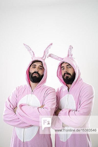 Zwei männliche Freunde mit Kaninchenkostümen vor weißem Hintergrund