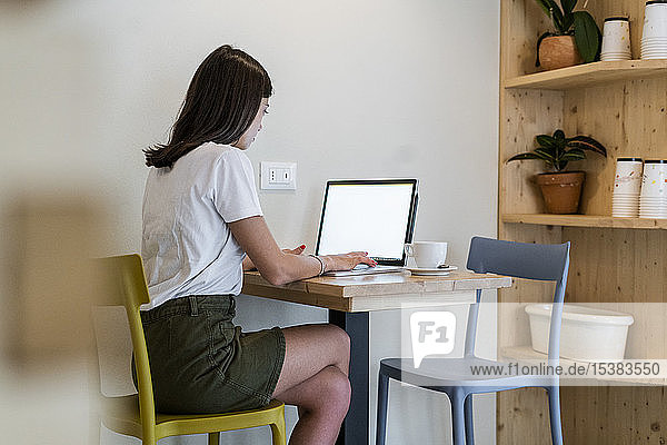 Junge Frau mit Laptop in einem Café