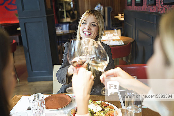 Smiling businesswomen meeting and clinking wine glasses in a restaurant