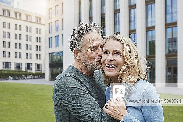 Glückliches reifes Paar umarmt und küsst sich in der Stadt