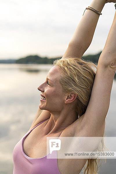 Happy young woman raising her arms at a lake