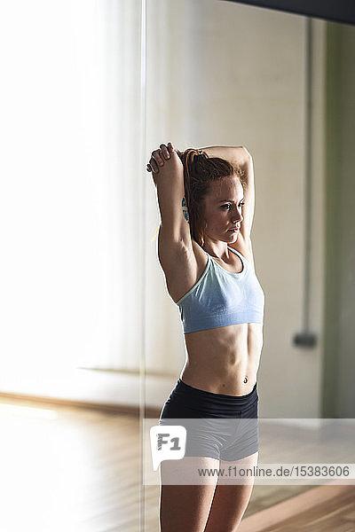 Sportliche junge Frau beim Stretching im Fitnessraum