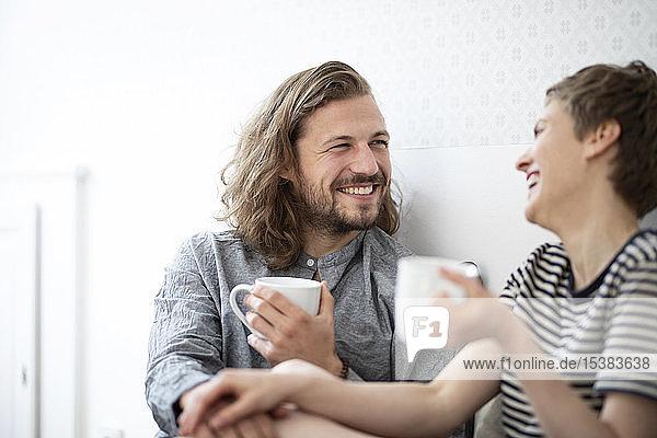Glückliches junges Paar hält zu Hause Becher