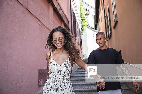 Porträt einer glücklichen jungen Frau  die mit ihrem Freund durch eine Gasse geht  Lecco  Italien