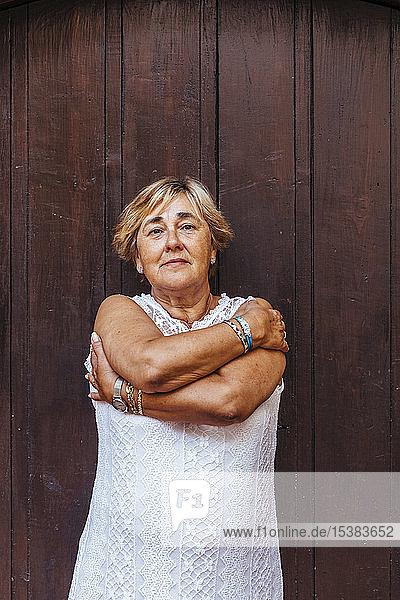 Porträt einer älteren Frau vor einer Holztür
