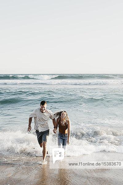 Glückliches junges Paar läuft am Meeresufer