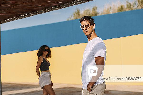 Kühles junges Paar mit Sonnenbrille steht im Sommer im Freien