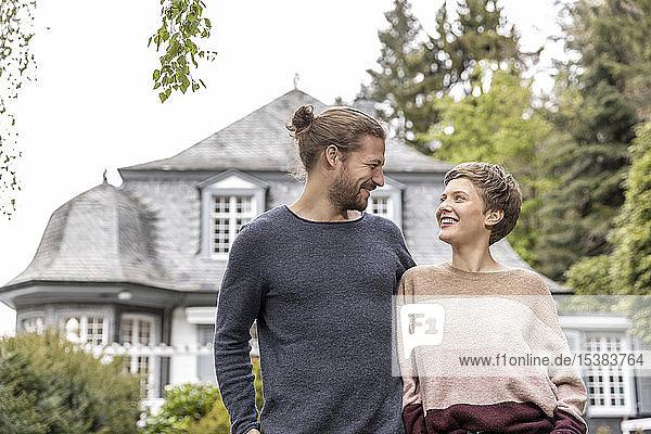 Lächelndes junges Paar im Garten ihres Hauses