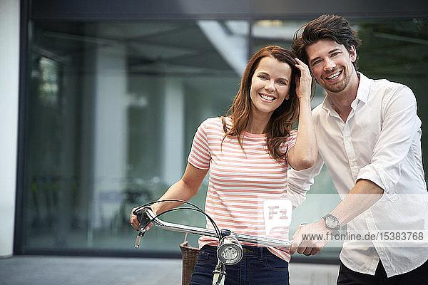Porträt eines glücklichen Paares mit Fahrrad in der Stadt