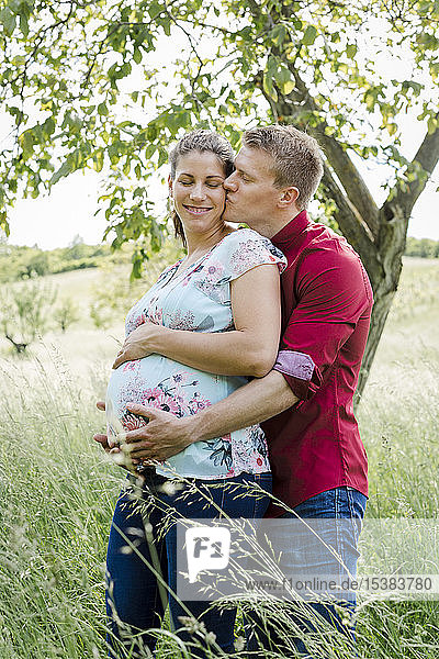 Schwangere Frau und Mann halten Babybauch  Mann küsst seine Frau