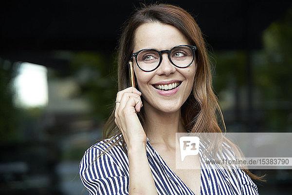 Glückliche Geschäftsfrau telefoniert in der Stadt