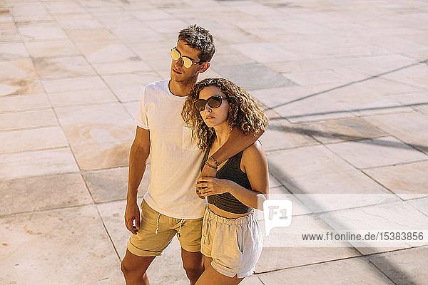 Junges Paar umarmt sich auf einem Platz
