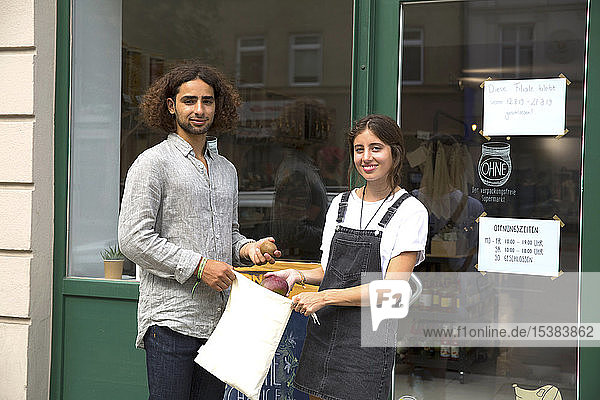 Portrait of smiling man and woman standing at entrance door of a store