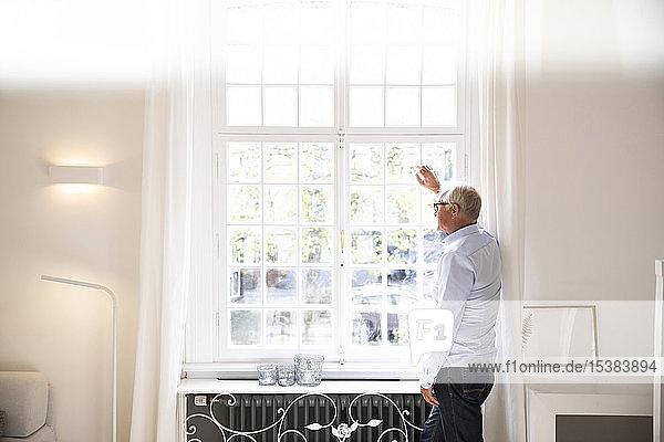 Älterer Mann schaut zu Hause aus dem Fenster