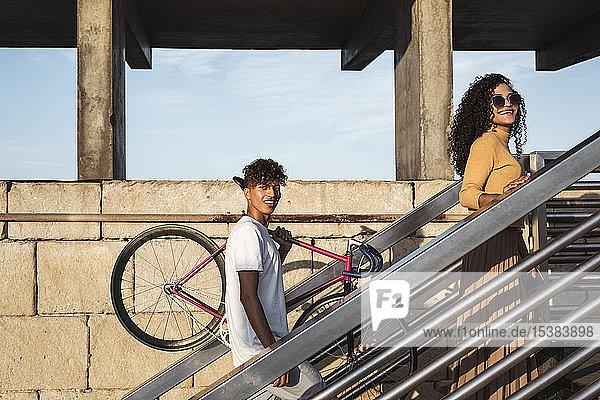 Junges Paar beim Treppensteigen  Fahrrad tragend Junges Paar beim Treppensteigen, Fahrrad tragend