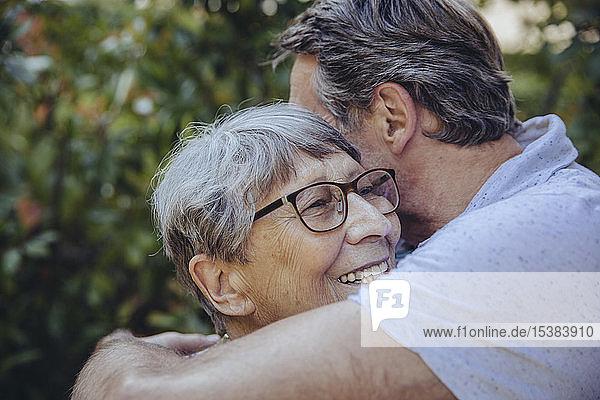 Erwachsener Sohn umarmt seine Mutter im Garten