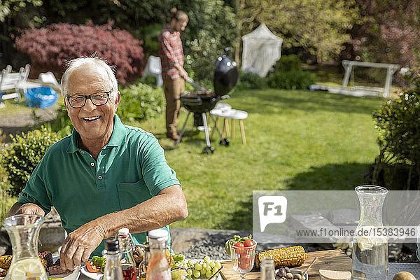 Porträt eines glücklichen älteren Mannes beim Mittagessen im Garten