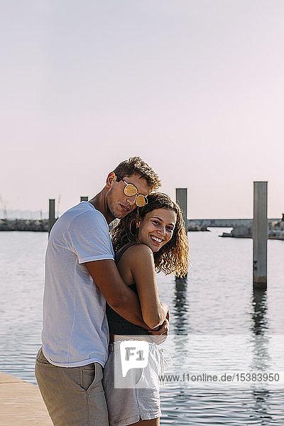 Glückliches junges Paar umarmt sich am Meer