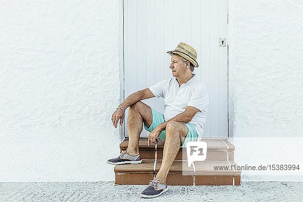 Älterer Tourist sitzt in einem Dorf auf der Treppe,  El Roc de Sant Gaieta,  Spanien