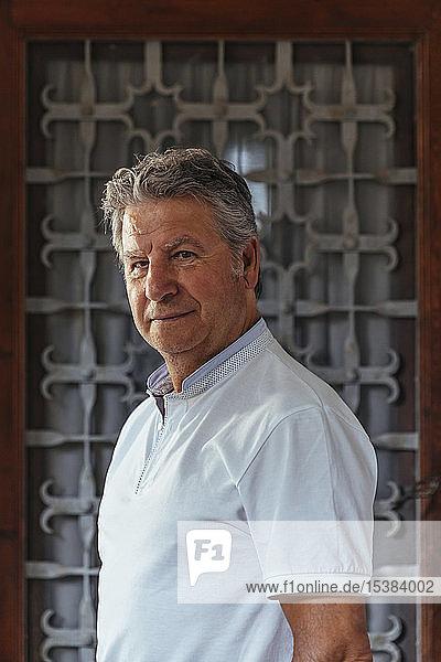 Porträt eines älteren Mannes vor einer Eisentür