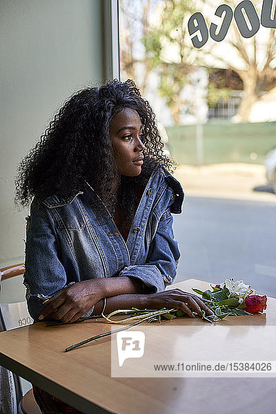 Portrait of young African woman with flowers on the table in a cafe  looking out of window