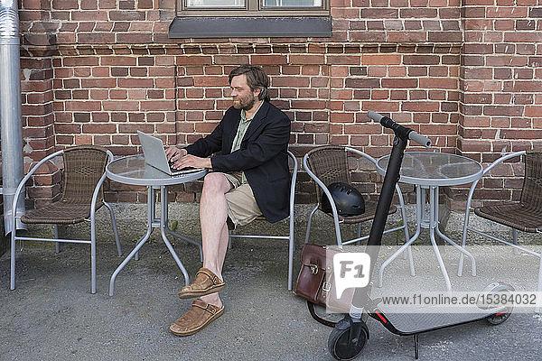 Mann mit Elektroroller sitzt mit Laptop im Straßencafé