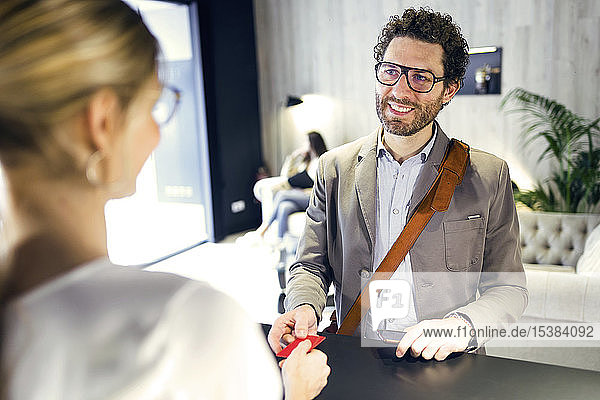 Smiling businessman handing over credit card at reception