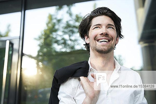 Porträt eines lachenden Geschäftsmannes in der Stadt