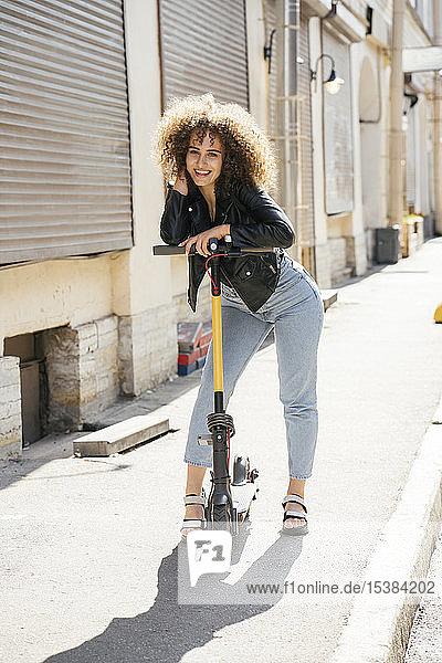 Porträt eines glücklichen Teenager-Mädchens  das mit einem Roller auf dem Bürgersteig steht