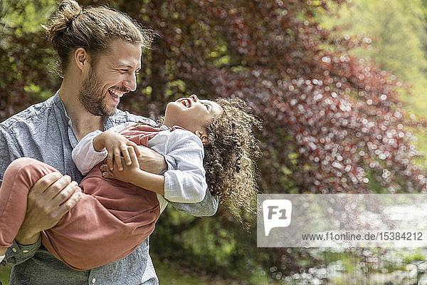 Glücklicher Vater amüsiert sich mit Sohn im Garten