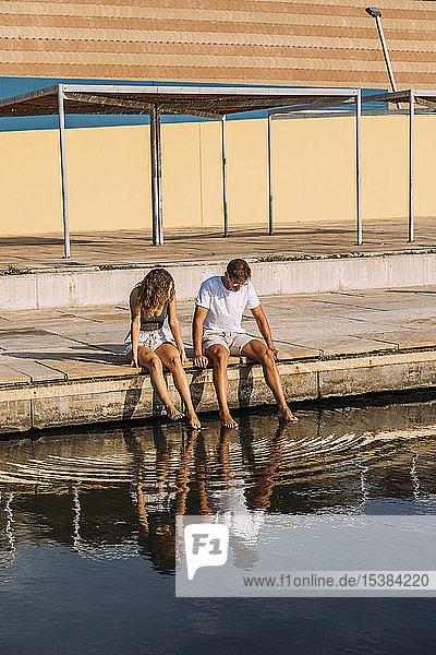 Junges Paar sitzt auf einer Mole am Meer