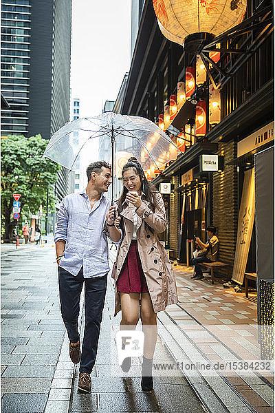 Glückliches Paar mit Regenschirm beim Spaziergang in Ginza  Tokio  Japan