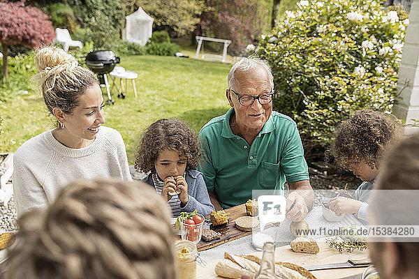 Großfamilie beim Mittagessen im Garten