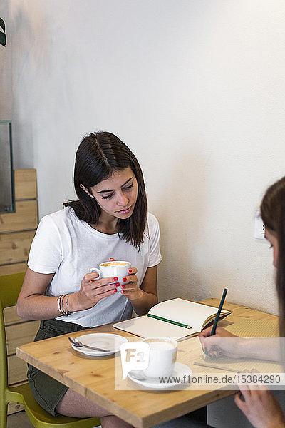 Zwei junge Frauen machen Notizen in einem Cafe